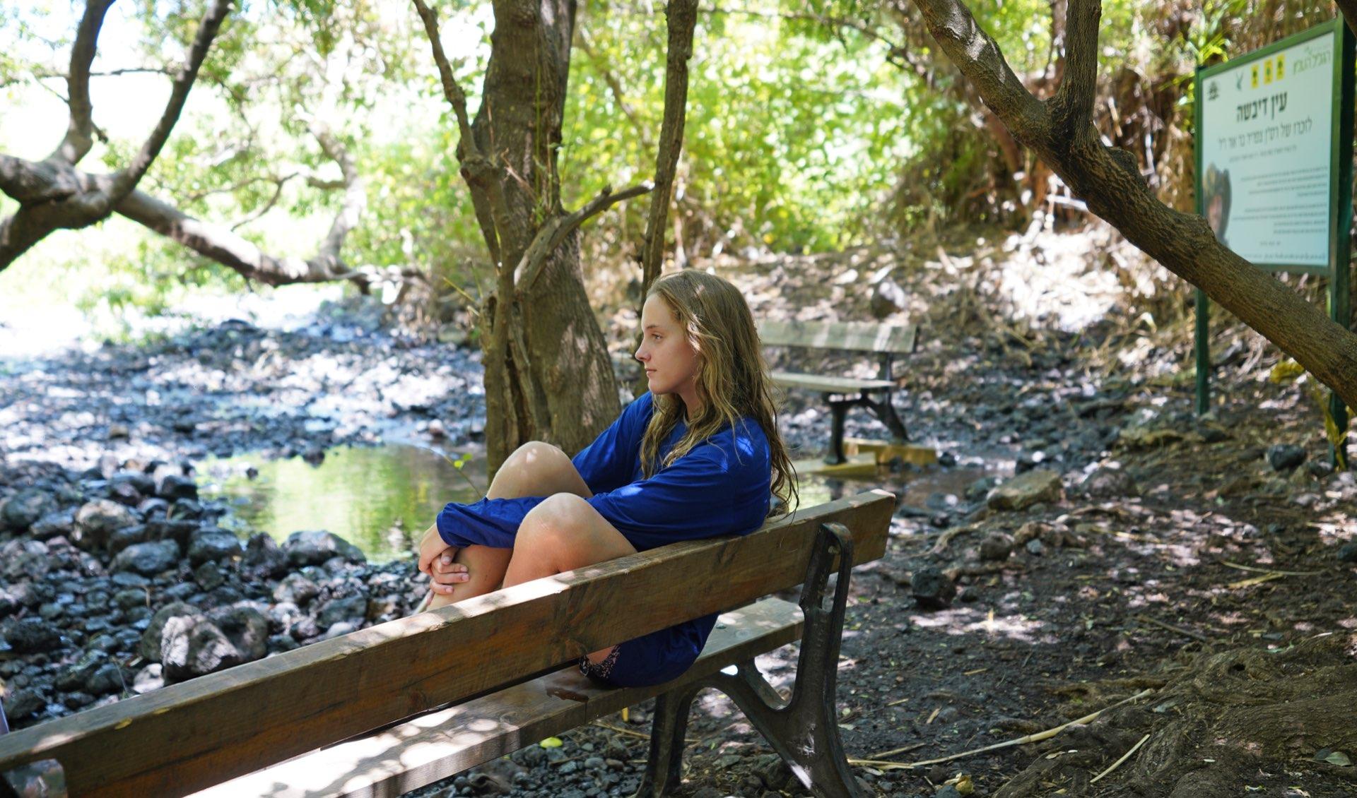 צעירה יושבת על ספסל בעין דבשה. צילום: יובל דקס