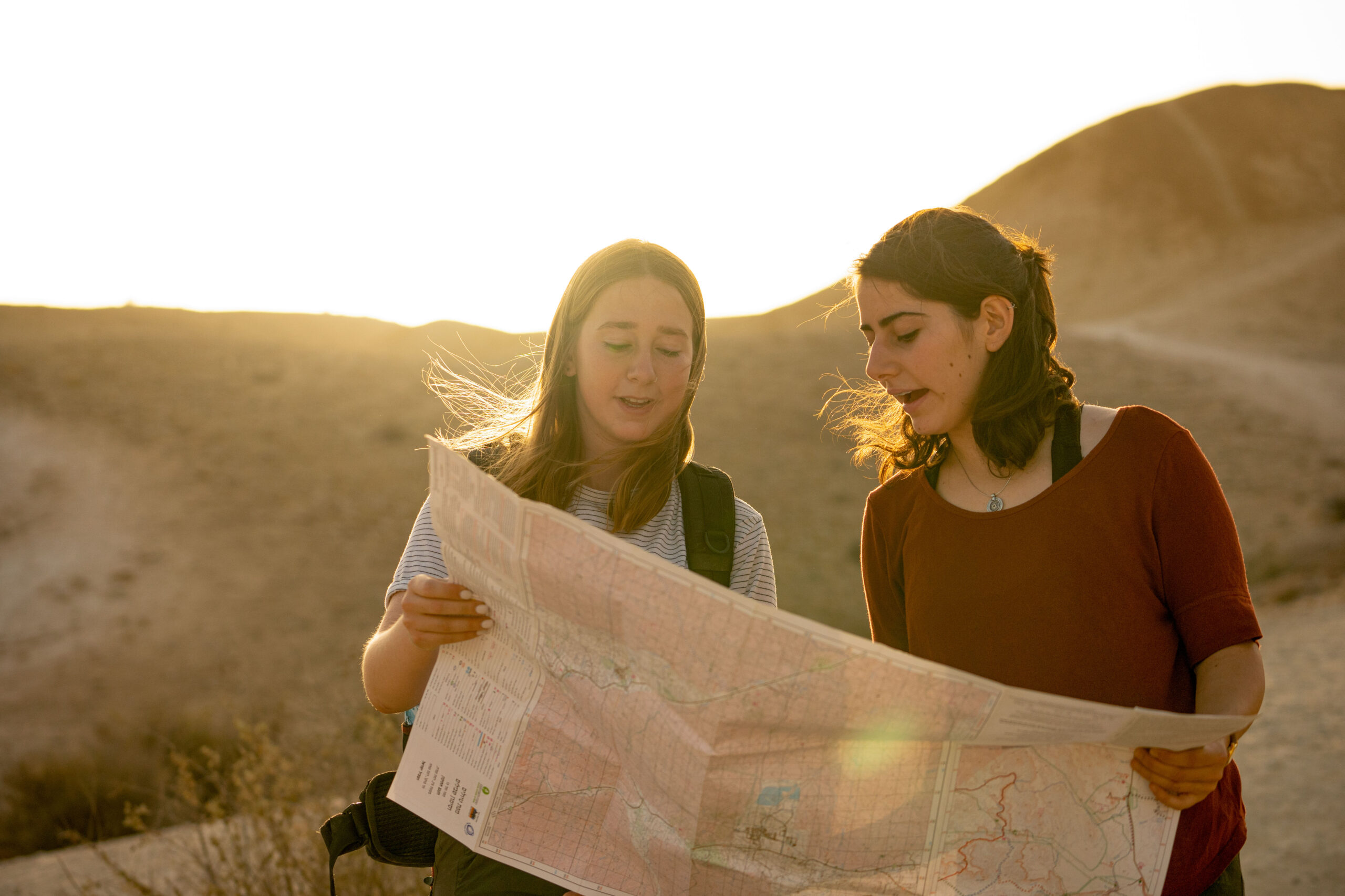 נערות מסתכלות במפה בנחל חווארים בשקיעה